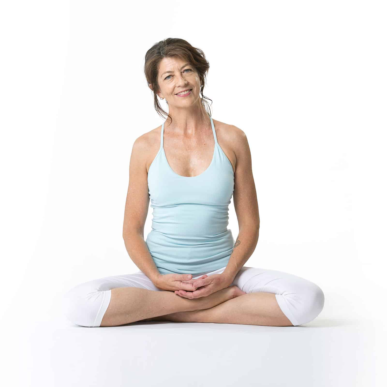 Sue Everett is cross legged in a welcoming yoga pose