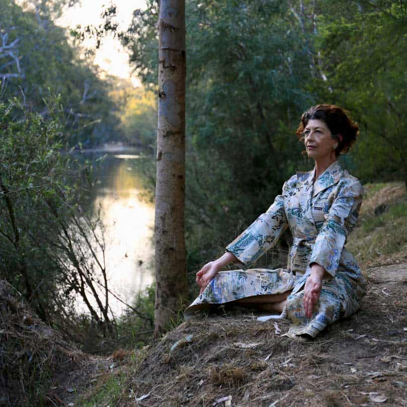 Sue Everett is meditating by a river